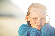 Portrait of smiling girl on the beach wrapped in a beach towel - ZEF003311
