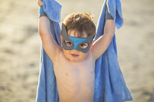 Little boy on the beach dressed up as a superhero with mask and towel - ZEF003410