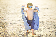 Little boy on the beach dressed up as a superhero with mask and towel - ZEF003413