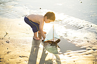 Boy on the beach playing with a toy wooden boat in the water - ZEF003428