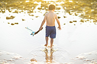 Boy wading with a toy wooden boat in the water - ZEF003422