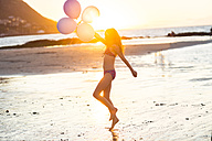 Girl on the beach holding balloons at sunset - ZEF003322
