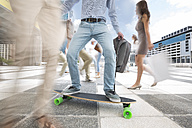 City commuter on a skateboard between a crowd of people - ZEF003965