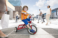 Boy riding a tricycle between a crowd of people in a city - ZEF003971