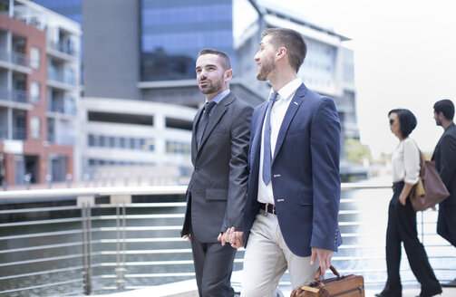 Gay couple travelling with business suits - ZEF002889