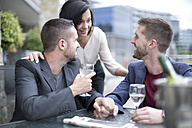 Gay couple sharing meal with a friend and drinking wine - ZEF002893