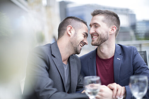 Gay couple sharing an intimate moment at a restaurant - ZEF002899