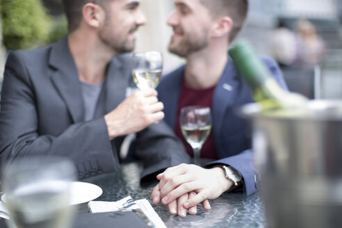 Gay couple sharing an intimate moment at a restaurant - ZEF002901