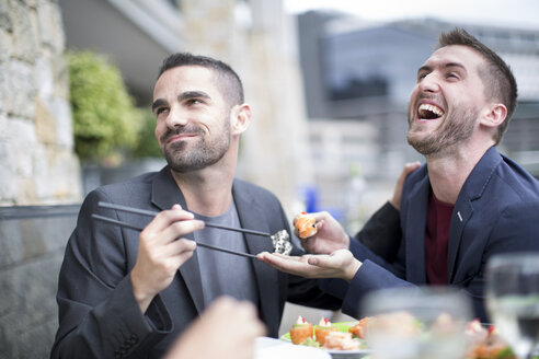 Gay couple eating sushi at outdoor restaurant - ZEF002904