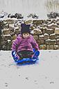 Little girl sitting on a sledge - LVF002545