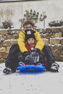 Brother and his little sister sitting on a sledge - LVF002557