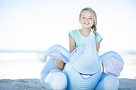 Smiling girl on beach sitting on an inflatable elephant - ZEF003323