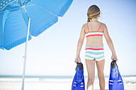 Girl on beach with flippers at sunshade - ZEF003328