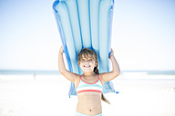 Smiling girl on beach holding a lilo - ZEF003336