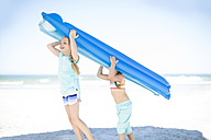 Two girls on beach carrying a lilo - ZEF003343