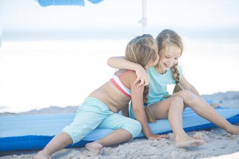 Two happy girls on beach sitting on a lilo - ZEF003352