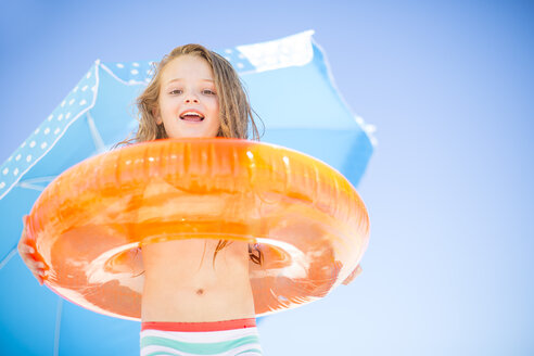 Smiling girl on beach holding an orange floating tyre - ZEF003356