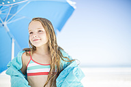 Smiling girl on beach drying off with a beach towel - ZEF003362
