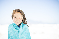 Smiling girl on beach wrapped in a towel - ZEF003370