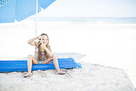 Girl on beach sitting on a lilo holding a starfish - ZEF003372