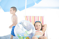 Smiling girl on beach relaxing on a beach chair with boy passing by - ZEF003390