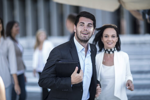 Smiling businessman in the city hand in hand with woman - ZEF003254