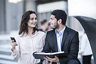Businessman and woman with diary and cell phone in the city - ZEF003257