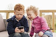 Little boy and girl looking at cell phone - NNF000301