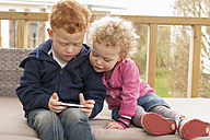 Little boy and girl looking at cell phone - NNF000357