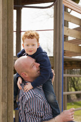 Father carrying son on playground - NNF000308