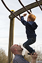 Father helping son on playground climbing on jungle gym - NNF000309