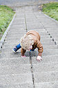 Little girl crawling up stairs - NNF000330