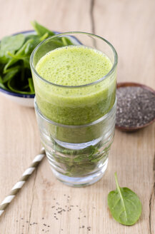 Glass of spinach smoothie, chia seeds and fresh spinach leaves on wood - ODF001002