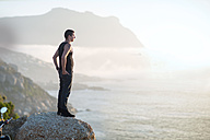 South Africa, Cape Town, motorcyclist standing on rock at the coast enjoying view - ZEF003605