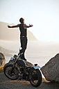 South Africa, Cape Town, motorcyclist standing on rock at the coast feeling free - ZEF003607