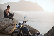 South Africa, Cape Town, motorcyclist sitting on rock at the coast enjoying view - ZEF003609