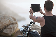 South Africa, Cape Town, motorcyclist at the coast taking pictures with digital tablet - ZEF003610