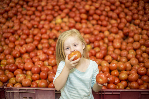 Little girl in front of tomato stall eating tomato - ZEF004188