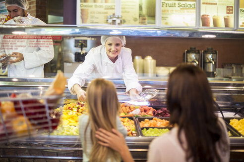 Mother and daughter buying fruit salad in supermarket - ZEF004197