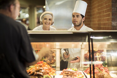 Male chef and assistant helping clients at food display - ZEF004199