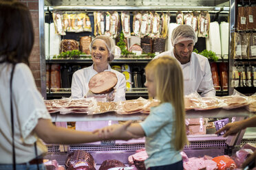 Customer with daughter buying ham at butchery - ZEF004930