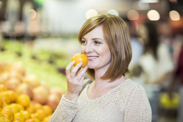 Young woman in supermarket holding orange - ZEF004207