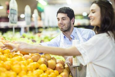 Shop assistant helping client choosing oranges - ZEF004210