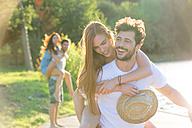 Happy young man carrying girlfriend piggyback - WESTF020715