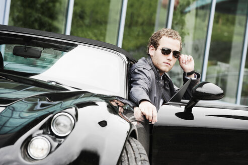 Young man wearing sunglasses sitting in black sports car - HHF005021