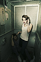 Attractive young woman in an old elevator with man sitting on ground - MEM000648