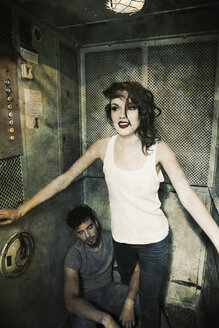 Attractive young woman in an old elevator with man sitting on ground - MEM000651