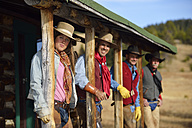 USA, Wyoming, cowgirl and three cowboys standing under a porch - RUEF001358