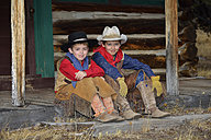 USA, Wyoming, two young cowboys sitting side by side - RUEF001416