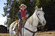 USA, Wyoming, portrait of young cowboy on his horse - RUEF001369